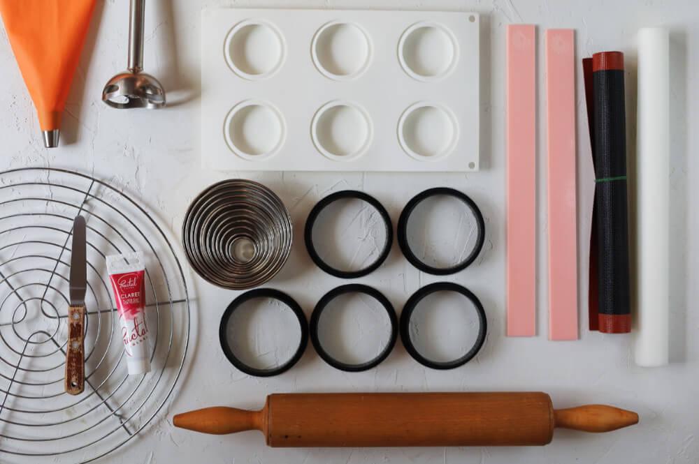 Czekoladowo-wiśniowe monoporcje - potrzebne narzędzia: ringi perforowane, silikonowa mata perforowana, papier do pieczenia, listwy dystansowe, okrągłe wykrawacze, forma silikonowa mini eclipse, barwnik żelowy, walek do ciasta, kratka do studzenia, blender, rękaw cukierniczy